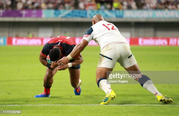 Joe Cokanasiga of England goes over to score his team's fourth try under a challenge from Paul Lasike of USA during the Rugby World Cup 2019 Group C...