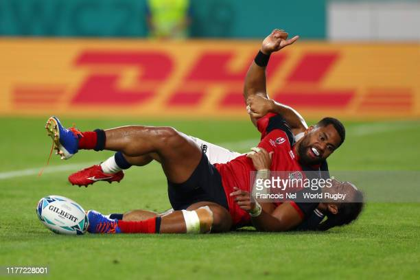 Joe Cokanasiga of England goes over to score his team's seventh try under a tackle from Mike Teo of USA during the Rugby World Cup 2019 Group C game...