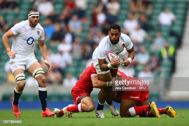 Joe Cokanasiga of England tackled by Ross Braude of Canada and Kainoa Lloyd of Canada during the Summer International Friendly match between England...