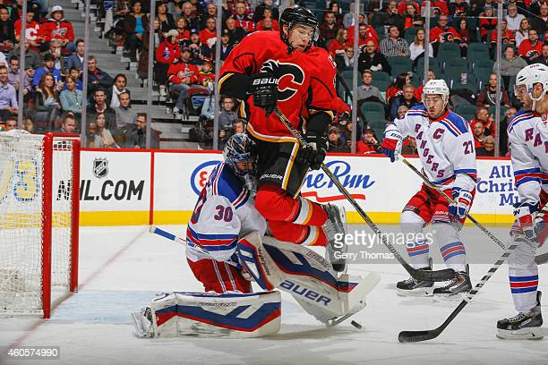 Joe Colborne of the Calgary Flames collides with goaltender Henrik Lundqvist of the New York Rangers at Scotiabank Saddledome on December 16 2014 in...