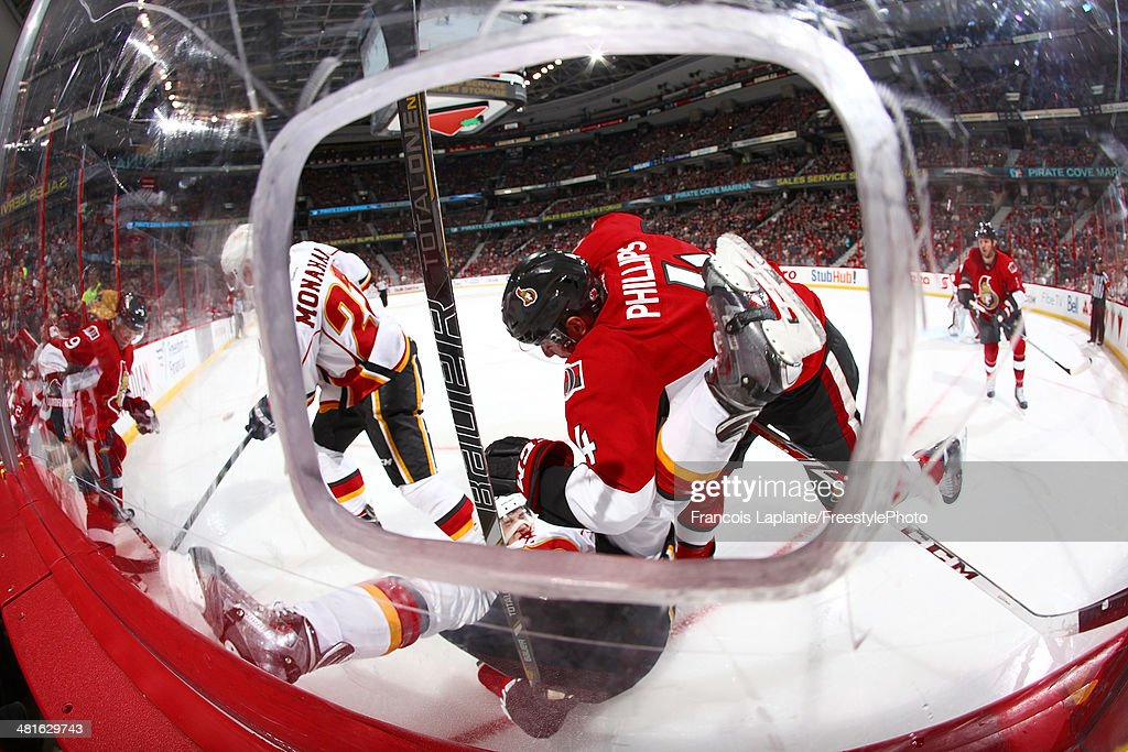 Joe Colborne #8 of the Calgary Flames falls as Chris Phillips #4 of the Ottawa Senators checks him during an NHL game at Canadian Tire Centre on March 30, 2014 in Ottawa, Ontario, Canada.