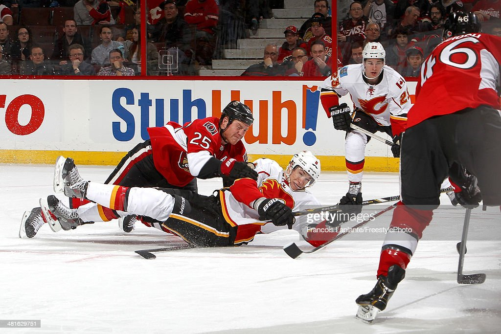 Joe Colborne #8 of the Calgary Flames falls on the ice and loses the puck as Chris Neil #25 of the Ottawa Senators trips him during an NHL game at Canadian Tire Centre on March 30, 2014 in Ottawa, Ontario, Canada.