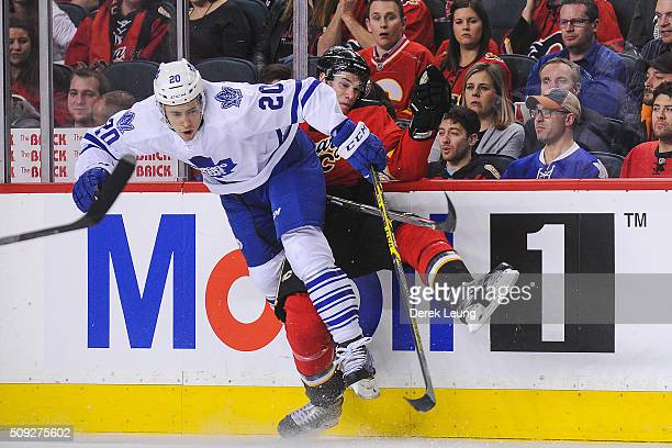 Joe Colborne of the Calgary Flames gets checked by Frank Corrado of the Toronto Maple Leafs during an NHL game at Scotiabank Saddledome on February 9...