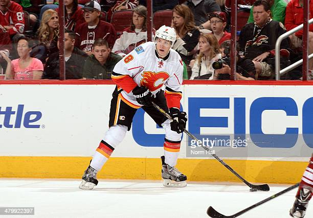 Joe Colborne of the Calgary Flames looks to pass the puck against the Phoenix Coyotes at Jobingcom Arena on March 15 2014 in Glendale Arizona