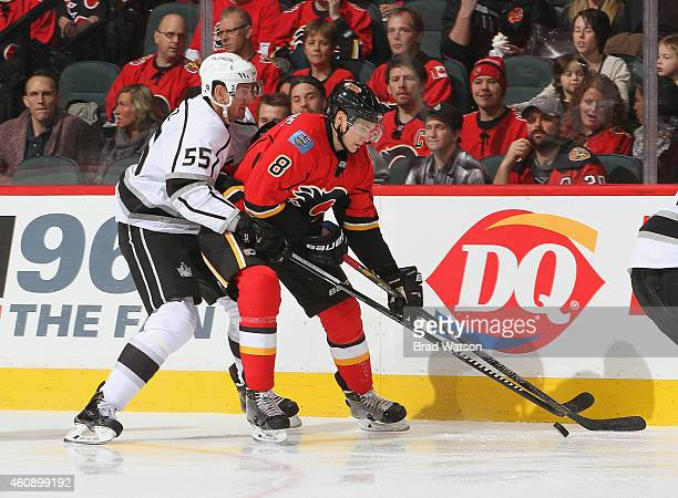 Joe Colborne of the Calgary Flames protects the puck against Jeff Schultz of the Los Angeles Kings at Scotiabank Saddledome on December 29 2014 in...