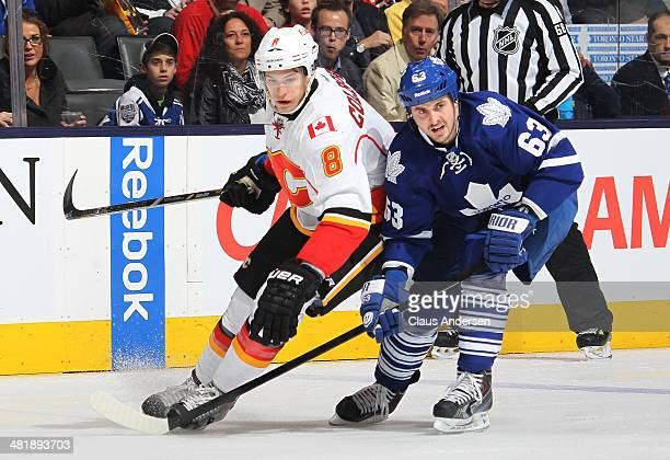 Joe Colborne of the Calgary Flames skates against David Bolland of the Toronto Maple Leafs during an NHL game at the Air Canada Centre on April 1...