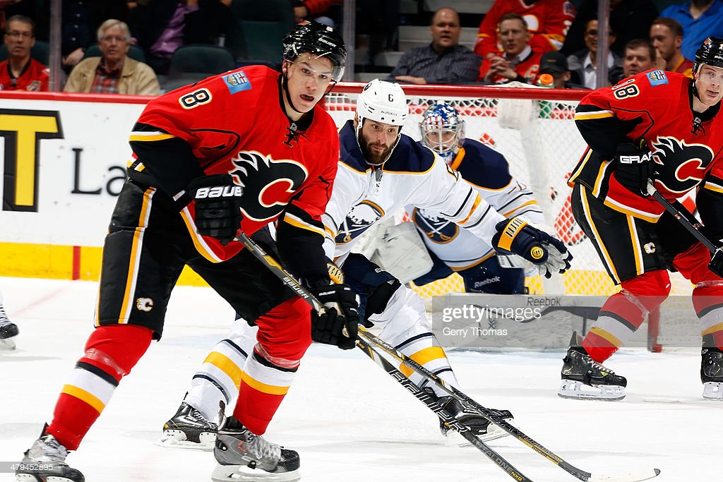 Joe Colborne #8 of the Calgary Flames skates against Mike Weber #6 of the Buffalo Sabres at Scotiabank Saddledome on March 18, 2014 in Calgary, Alberta, Canada.