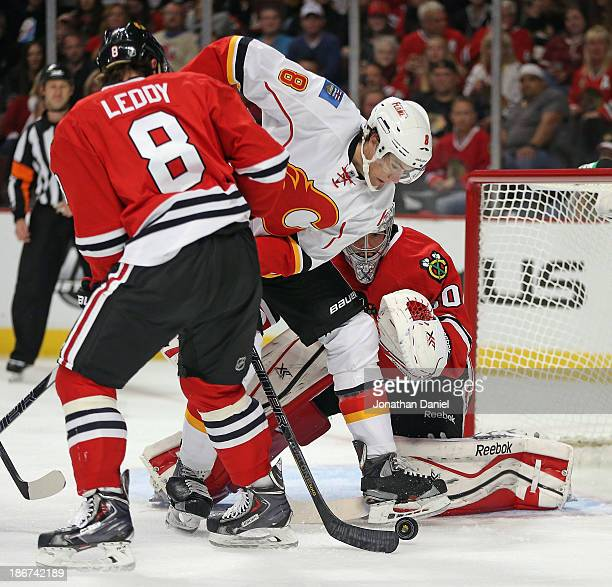 Joe Colborne of the Calgary Flames tries to get off a shot between Nick Leddy and Corey Crawford of the Chicago Blackhawks at the United Center on...