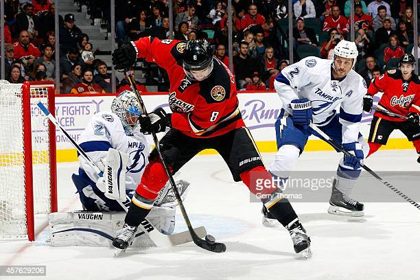 Joe Colborne of the Calgary Flames tries to re-direct a puck past goalie Evgeni Nabokov of the Tampa Bay Lightning at Scotiabank Saddledome on...