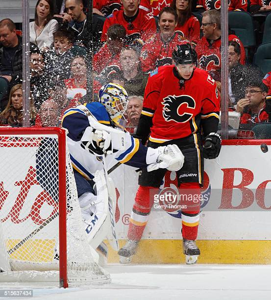 Joe Colborne of the Calgary Flames tries to stop a clearing attempt by Anders Nilsson of the St Louis Blues at Scotiabank Saddledome on March 14 2016...