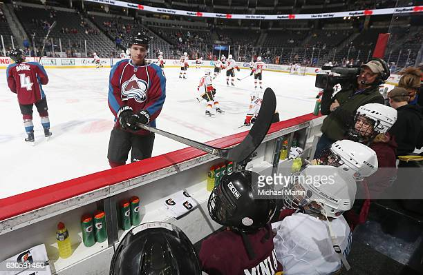 Joe Colborne of the Colorado Avalanche taps a fan on the helmet during warm ups prior to the game against the Calgary Flames at the Pepsi Center on...