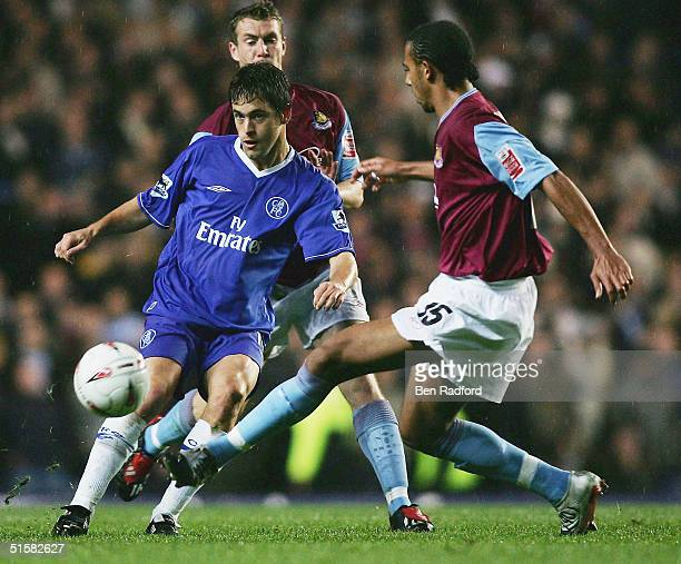 Joe Cole of Chelsea chips the ball past Anton Ferdinand of West Ham during the Carling Cup Third Round match between Chelsea and West Ham United at...