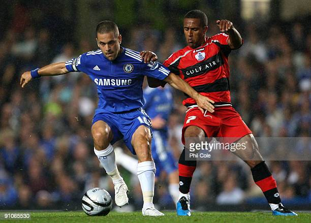 Joe Cole of Chelsea gets tackled by Wayne Routledge of Queens Park Rangers during the Carling Cup third round match between Chelsea and Queens Park...