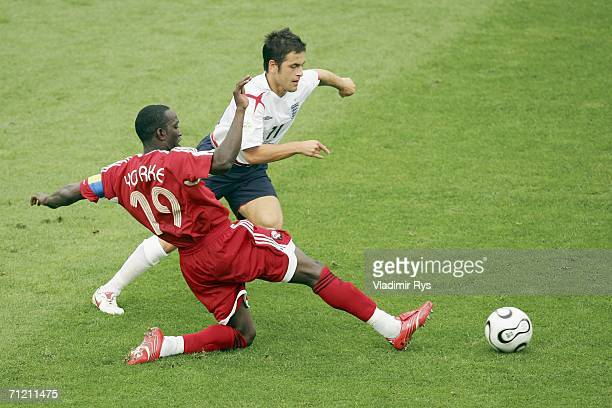 Joe Cole of England is tackled by Dwight Yorke of Trinidad and Tobago during the FIFA World Cup Germany 2006 Group B match between England and...