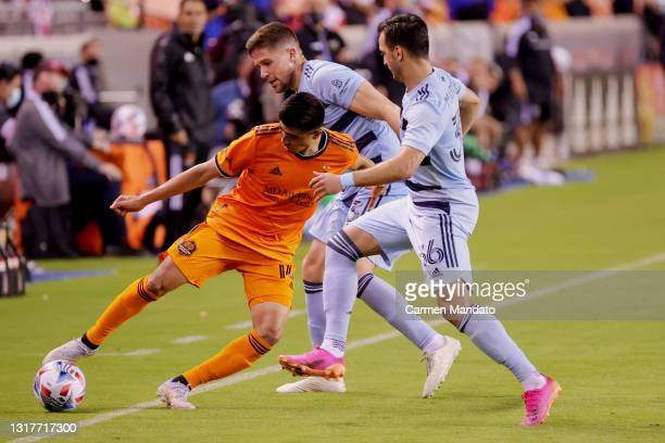 Joe Corona of Houston Dynamo reaches for the ball ahead of defenders Luis Martins of Sporting Kansas City during the second half at BBVA Stadium on...
