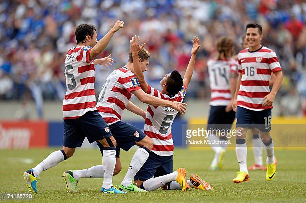 Joe Corona of the United States celebrates with his teammates after scoring a goal in the first half against El Salvador during the 2013 CONCACAF...