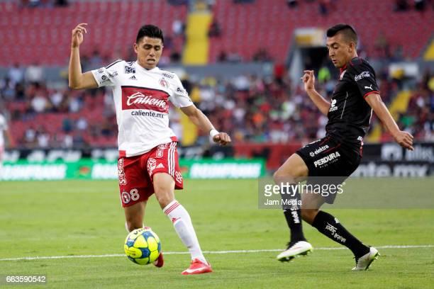 Joe Corona of Tijuana and Daniel Alvarez of Atlas vie for the ball during the 12th round match between Atlas and Tijuana as part of the Torneo...