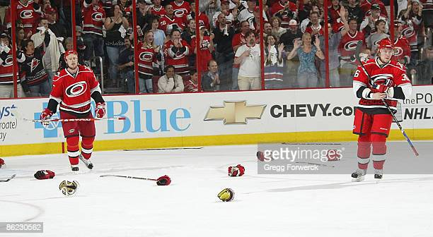 Joe Corvo and Jussi Jokinen of the Carolina Hurricanes skate through scattered sticks and gloves after a melee with the New Jersey Devils during Game...