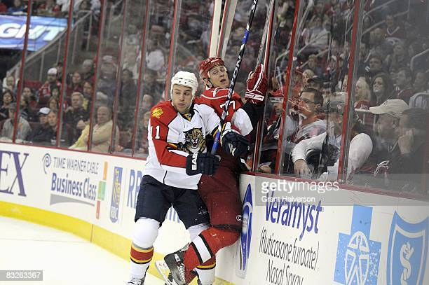 Joe Corvo of the Carolina Hurricane is checked by Gregory Campbell of the Florida Panthers on October 10, 2008 at the RBC Center in Raleigh, North...