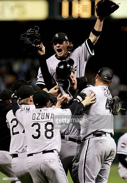 Joe Crede of the Chicago White Sox jumps onto his teammates in celebration after winning Game Four of the 2005 Major League Baseball World Series...