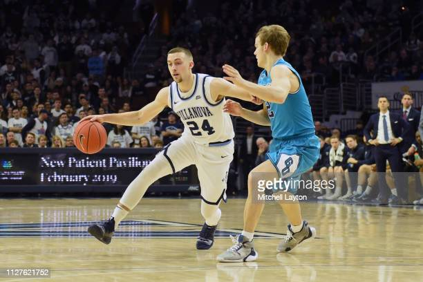 Joe Cremo of the Villanova Wildcats dribbles by James Akinjo of the Georgetown Hoyas during a college basketball game at the Wells Fargo Center on...