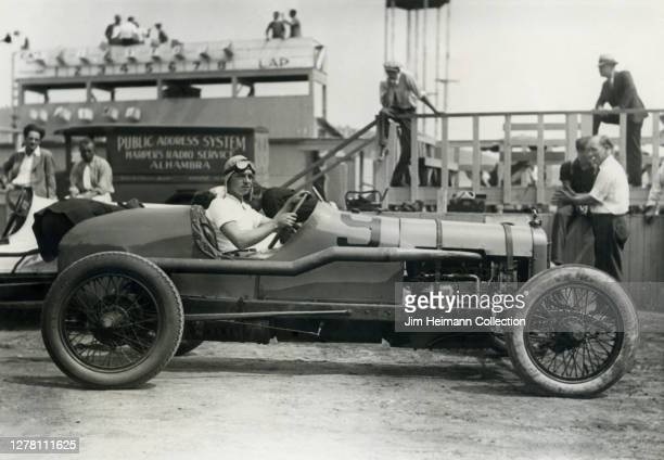 Joe Crocker poses in a race car at the speedway with a group of spectators milling about in the background, circa 1935.