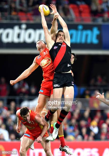 Joe Daniher of the Bombers and Steven May of the Suns compete for the mark during the round 22 AFL match between the Gold Coast Suns and the Essendon...