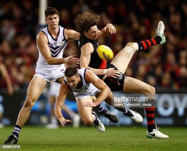Joe Daniher of the Bombers collides with Sam Collins and Ethan Hughes of the Dockers during the 2017 AFL round 23 match between the Essendon Bombers...