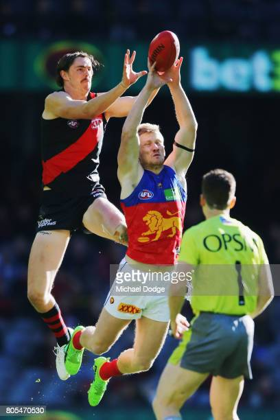 Joe Daniher of the Bombers competes for the ball over Nick Robertson of the Lions during the round 15 AFL match between the Essendon Bombers and the...