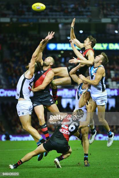 Joe Daniher of the Bombers flys high into the backs of Tom Bellchambers of the Bombers and Charlie Dixon of Port Adelaide during the round four AFL...