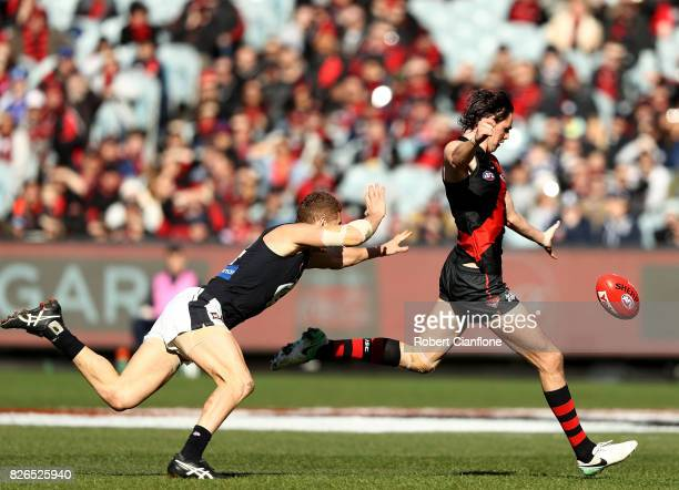 Joe Daniher of the Bombers gets his kick away from Liam Jones of the Blues during the round 20 AFL match between the Essendon Bombers and the Carlton...
