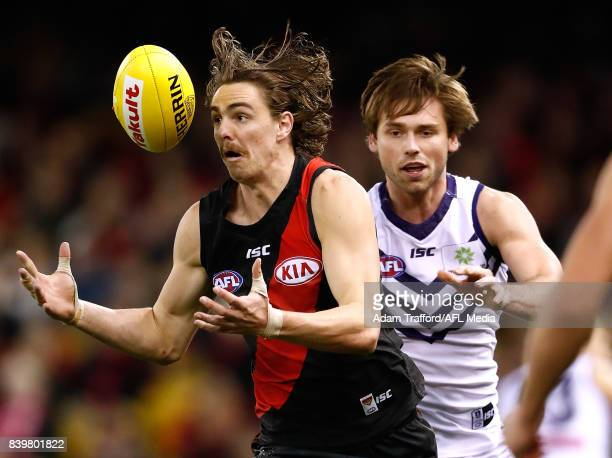 Joe Daniher of the Bombers juggles the ball ahead of Joel Hamling of the Dockers during the 2017 AFL round 23 match between the Essendon Bombers and...