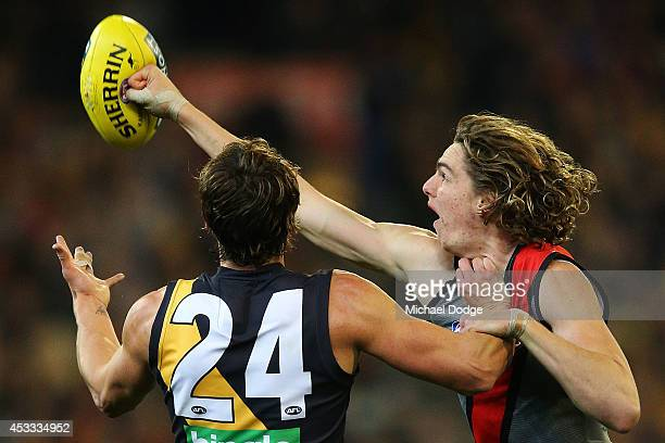 Joe Daniher of the Bombers punches the ball away from Ben Griffiths of the Tigers during the round 20 AFL match between the Richmond Tigers and the...