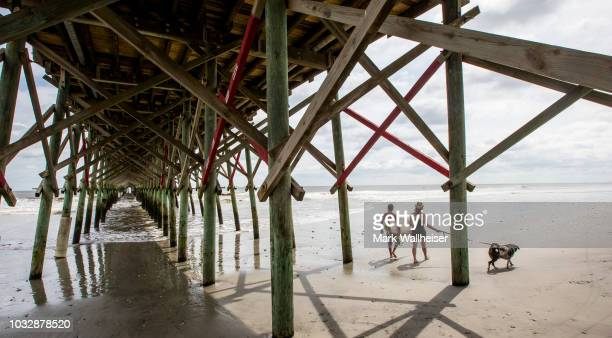 Joe Davis left and Lea Corum with her dog Gunner walk under the Folly Beach pier on September 13 2018 in Charleston South Carolina United States...
