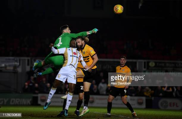 Joe Day and Fraser Franks of Newport County compete with Kieran Agard of Milton Keynes Dons during the Sky Bet League Two match between Newport...