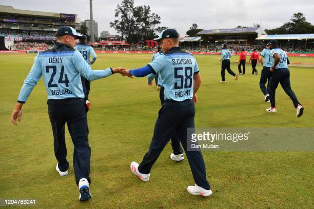 Joe Denly of England and Tom Curran of England high five as they take to the field during the Second One Day International match between England and...