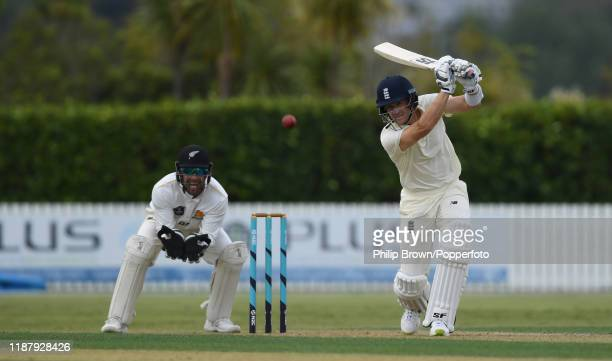 Joe Denly of England hits out watched by Tom Blundell of New Zealand XI at Cobham Oval on November 16, 2019 in Whangarei, New Zealand.