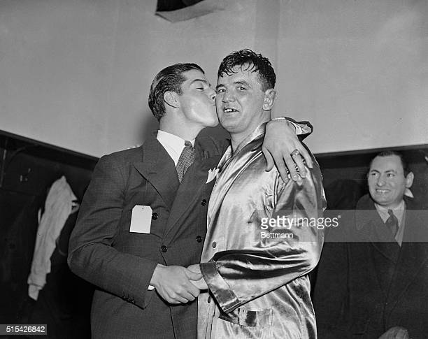 Joe DiMaggio hard hitting outfielder for the New York Yankees bestows a kiss on James J Braddock former world's heavyweight champion after the latter...