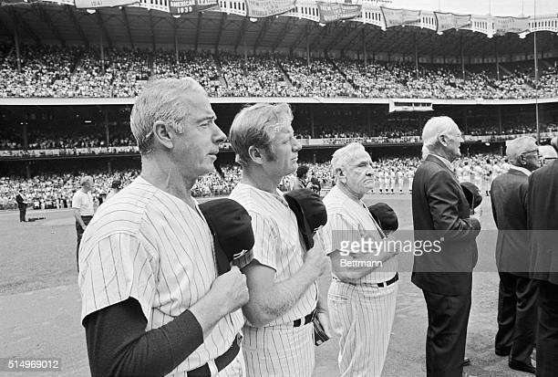 Joe DiMaggio, Mickey Mantle, and Casey Stengel salute the flag during the National Anthem played before the annual old-timers game at Yankee Stadium...