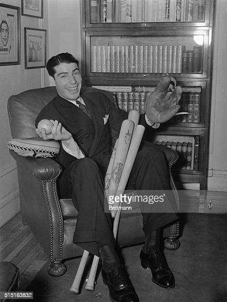 Joe DiMaggio, New York Yankee star, who was voted the most valuable player by sports writers, fondled the instruments of his craft that brought him...