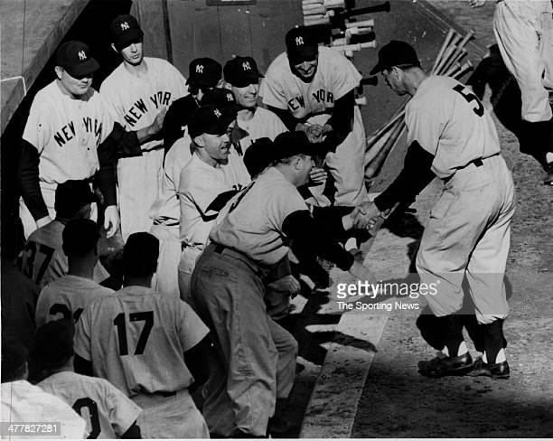 Joe DiMaggio of the New York Yankees celebrates with teammates in the dugout after DiMaggio hit a home run during Game Four of the 1951 World Series...
