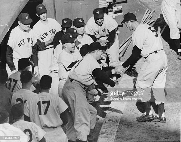 Joe DiMaggio of the New York Yankees hits a home run and gets congratulated by teammates as he enters the dugout during the 1951 World Series against...