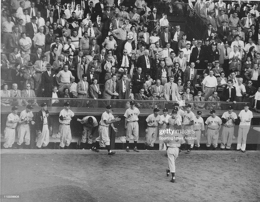 Joe DiMaggio of the New York Yankees is congratulated by teammates after hitting a home run in the 1949 World Series against the Brooklyn Dodgers.
