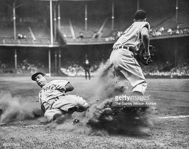 Joe DiMaggio of the New York Yankees is out at third on a force play as third baseman George Kell holds the ball in the secound inning on September...