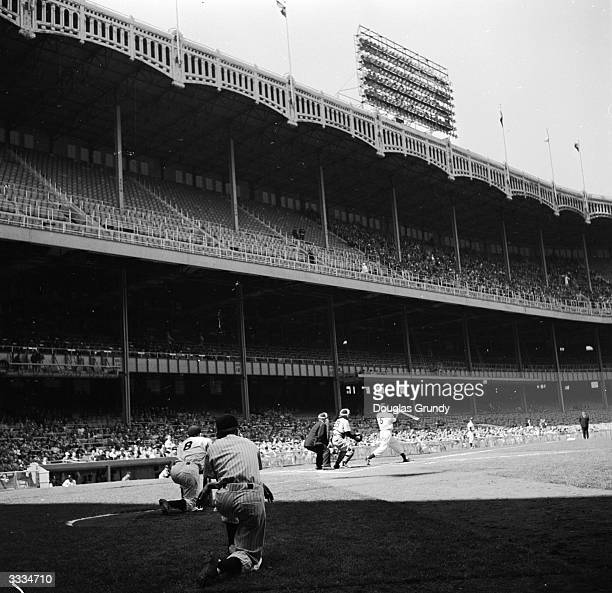 Joe DiMaggio of the New York Yankees swings at a pitch while Yogi Berra waits on deck during a game at Yankee Stadium in the Bronx New York