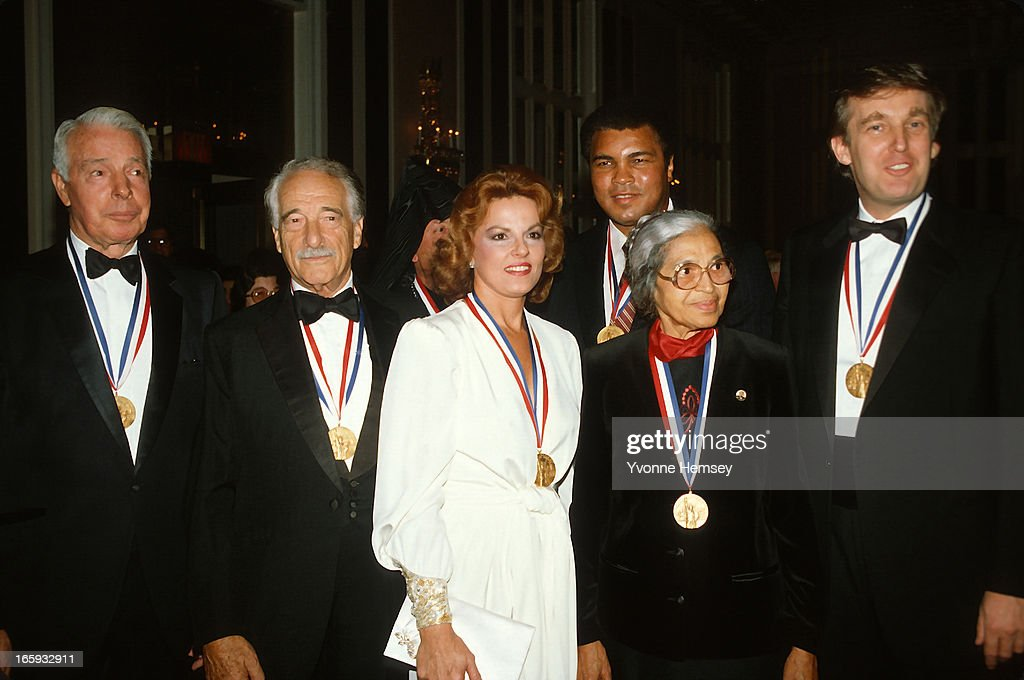 Joe DiMaggio, Victor Borge, Anita Bryant, Muhammad Ali, Rosa Parks, and Donald Trump pose for a photograph after receiving the Ellis Island Medal of Honor October 27, 1986 in New York City.
