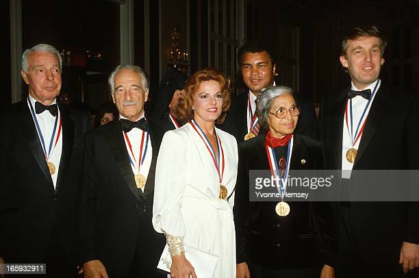Joe DiMaggio Victor Borge Anita Bryant Muhammad Ali Rosa Parks and Donald Trump pose for a photograph after receiving the Ellis Island Medal of Honor...