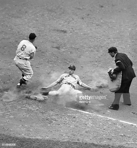 Joe DiMaggio Yankee outfielder is shown sliding into third base in the 7th inning of the Yankees-Indians game at Cleveland yesterday. DiMaggio got...