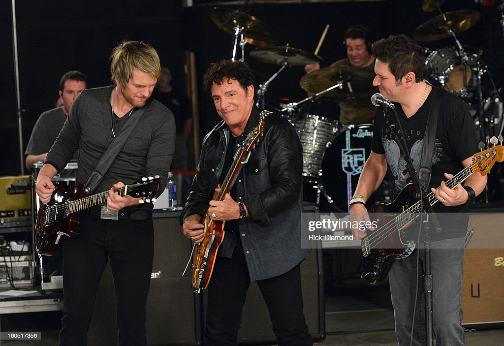 Joe Don Rooney (L) and Jay DeMarcus (R) of Rascal Flatts perform with Neal Schon of Journey (center) during CMT Crossroads: Journey and Rascal Flatts Live from Super Bowl XLVII rehearsals on February 1, 2013 in New Orleans, Louisiana.