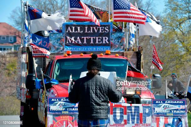 Joe Douillette a counterprotester and school teacher blocks a truck as it takes part in the Liberate Massachusetts rally outside the home of...